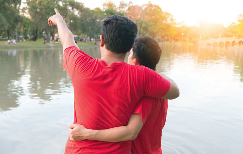 Rear View Of Homosexual Couple Standing By Lake During Sunset