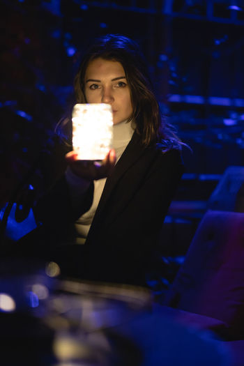 Portrait of beautiful woman showing glowing jar at night