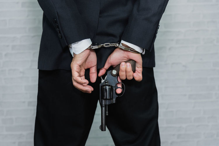 Midsection Rear View Of Businessman With Handcuffs Holding Gun