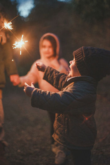 Rear view of people holding sparkler at night