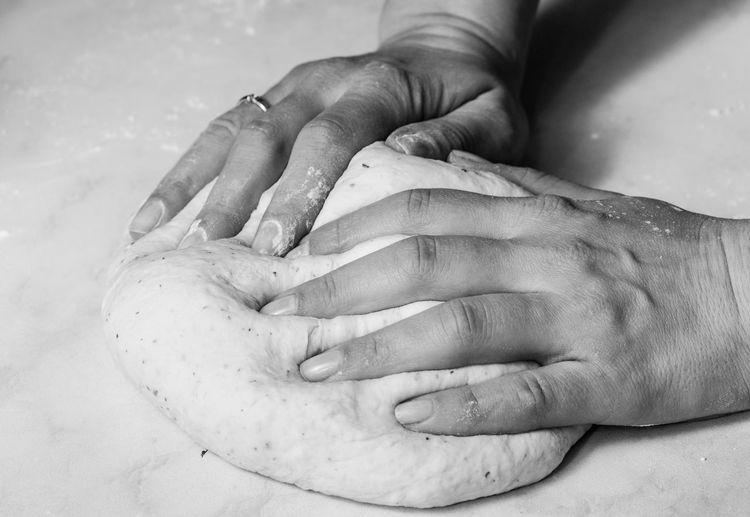 Cropped hands of person making dough on marble