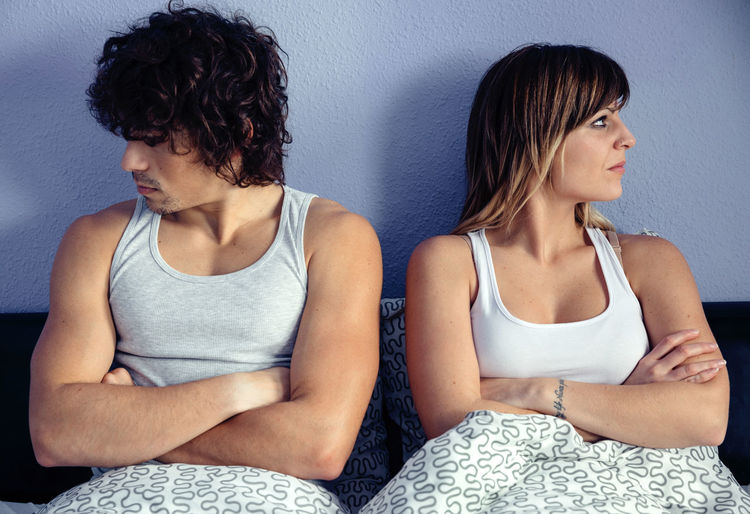 Angry couple sitting on bed at home