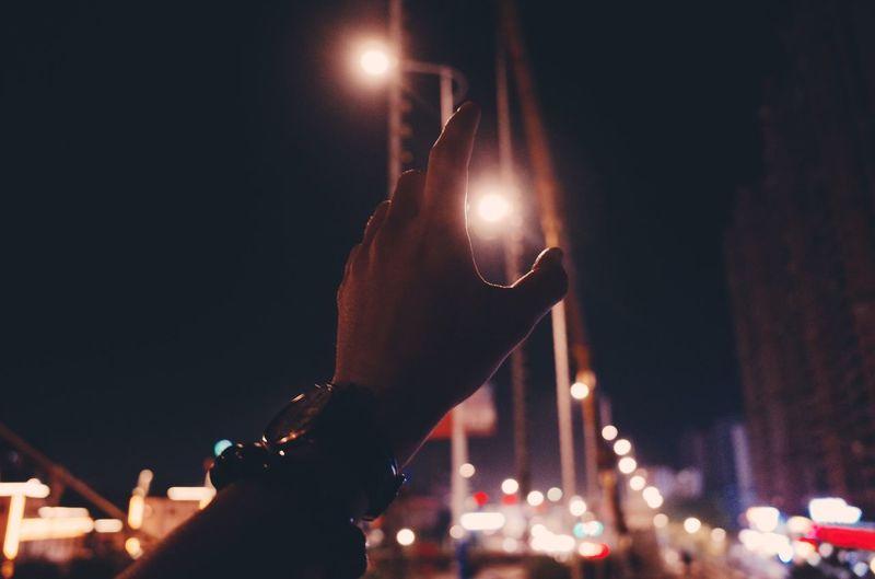Person holding illuminated street light in city at night