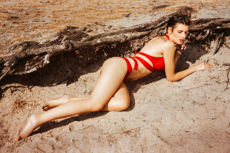 High angle view of sensuous model in red bikini posing at beach
