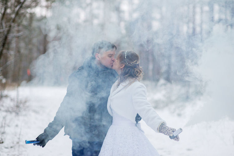 Close-up of couple with distress flare kissing against tree during winter