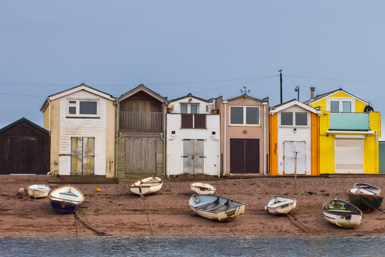 Boats scattered on the beach of the River Teign in front of colorful boat houses Orange Teign Estuary Architecture Back Beach Beach Boathouse Boats Building Exterior Day Fishing Land Mooring River Scattered Side By Side Teignmouth Transportation White Yellow