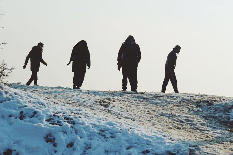Low angle view of people on snow against clear sky