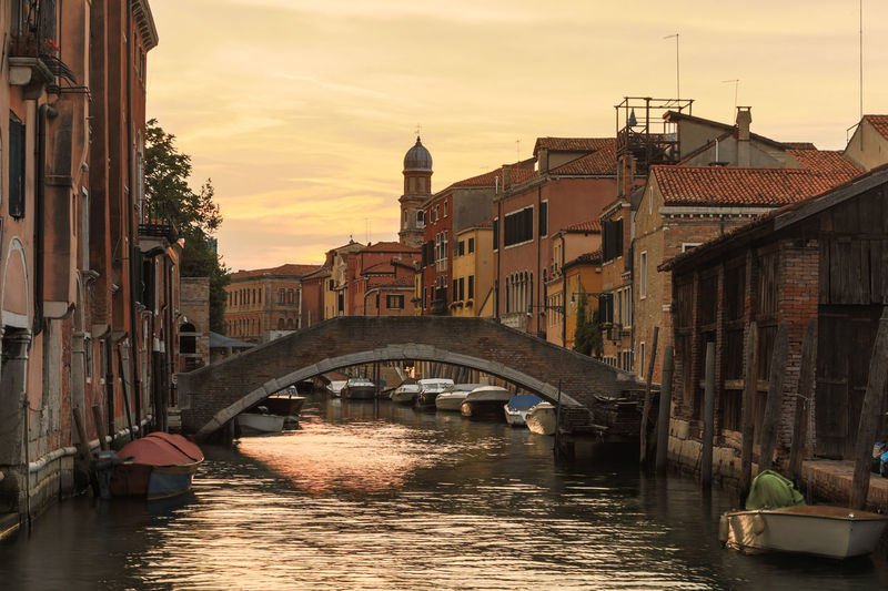 Bridge over canal amidst buildings against sky during sunset