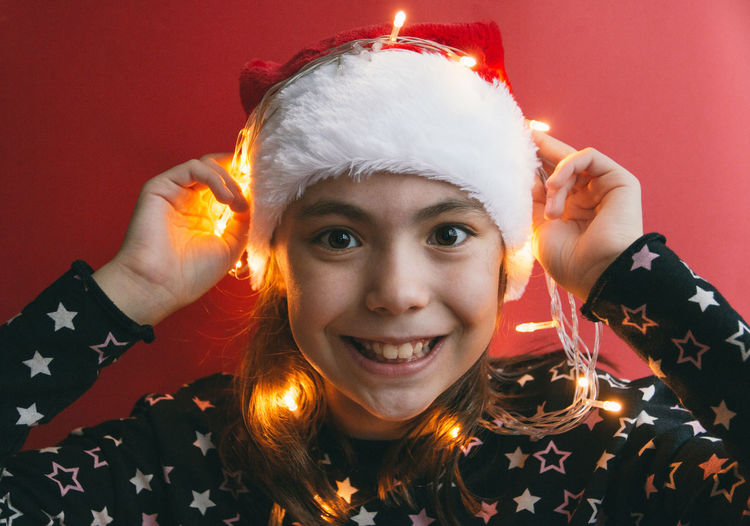 Girl with illuminated string light against red wall