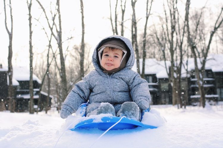 Portrait Of Baby Boy On Sled Against Trees At Snow Covered Field