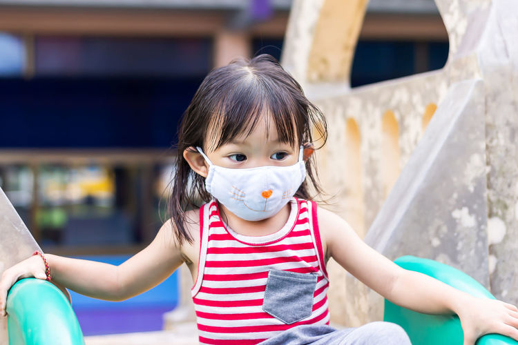 Close-up of cute girl wearing mask sitting on slide