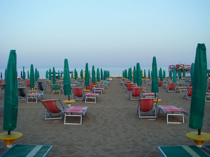 Beach in the morning without people. Empty lounge chairs and sunshades of bright color, neatly placed Chair Absence Seat Sky In A Row No People Empty Day Water Tranquility Arrangement Outdoors See Sunbeam Beach Vacations Summer Ressort Tourism Sunumbrella Relax Rest Leisure Parasol Idyllic