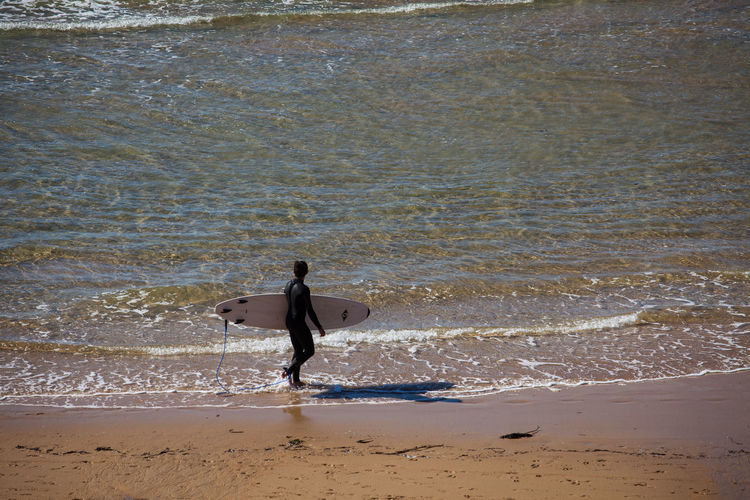 High angle view of man holding surfboard walking on shore