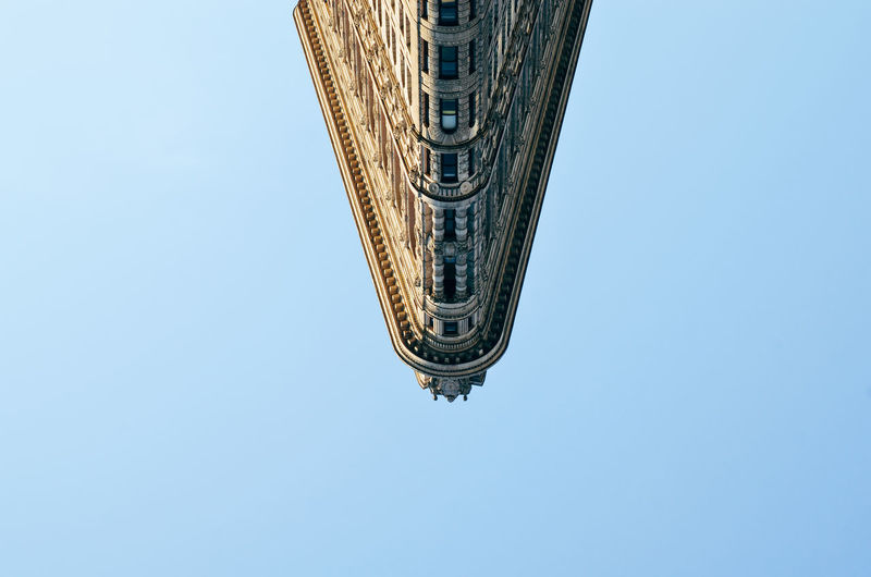 Upside down image of flatiron building against clear sky