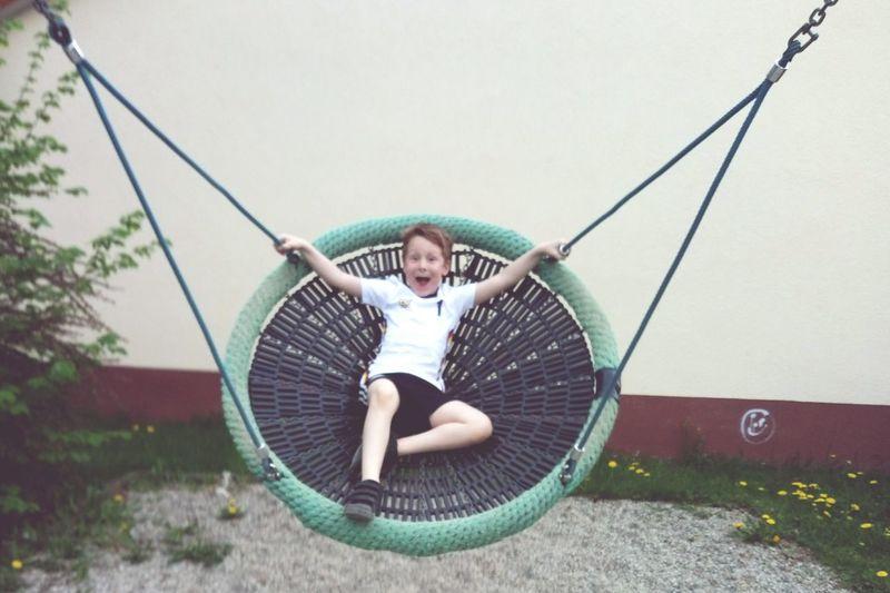 Portrait of playful boy enjoying on swing against wall
