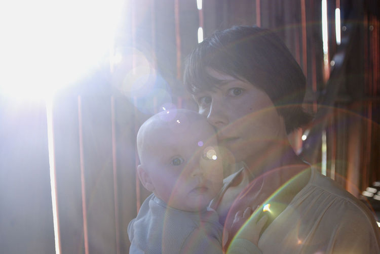 A mother carrying her baby boy. Bonding Child Childhood Emotion Family Innocence Lens Flare Love Son Sunlight Togetherness Two People