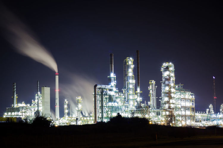 Illuminated petrochemical plant against sky at night