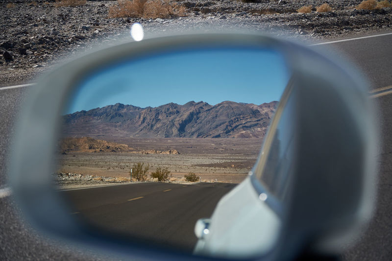 Reflection of mountains on side-view mirror of car