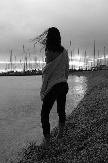 While the wind blew and the storm arrived, in my heart I felt the distance from you. Boats And Sea Casual Clothing Lonely Girl Nautical Vessel Person Seaport Of Ostia Stones On A Beech Scene Sun Behind The Clouds The Wind Blows Among The Hair