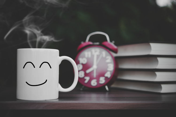 Close-up of clock and cup on table