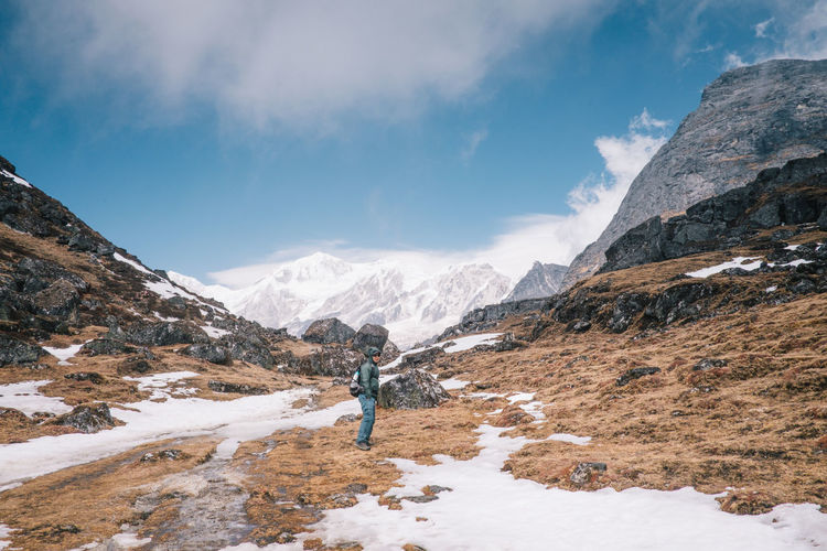 Scenic view of snowcapped mountains with man on rock against sky