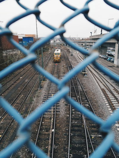 High Angle View Of Train On Railroad Track Seen Through Chainlink Fence