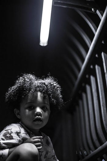 Portrait of kid with curly hair sitting in illuminated room