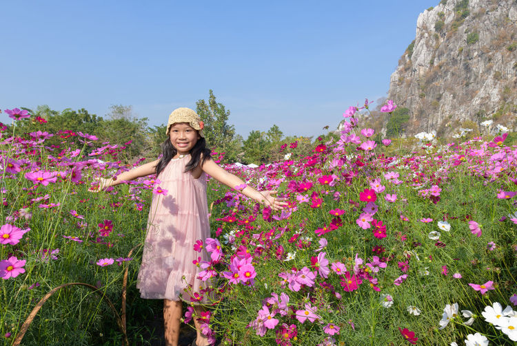 Portrait of smiling young woman standing by pink flowering plants
