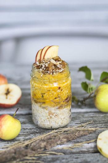 Apple porridge in jar with fruits on table