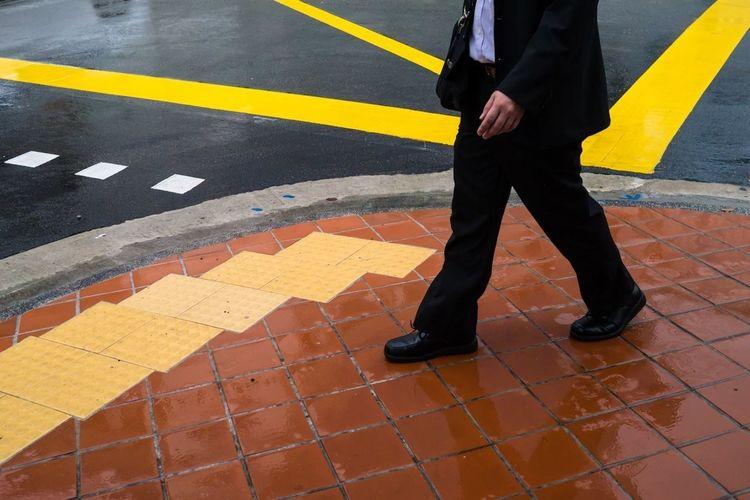Low section view of businessman walking on sidewalk