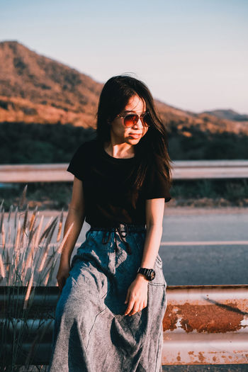 Young woman wearing sunglasses on railing against sky