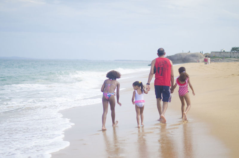 Sea Water Beach Land Group Of People Childhood Child Girls Women Family Real People Leisure Activity Togetherness Full Length Men Holiday Boys Trip Vacations Horizon Over Water Sister Positive Emotion Daughter