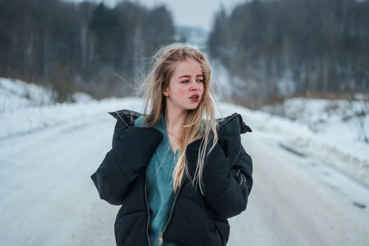 Young woman standing on snow
