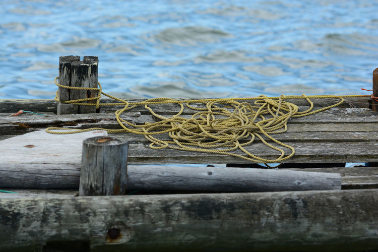 Close-up of rope tied to wooden post at sea