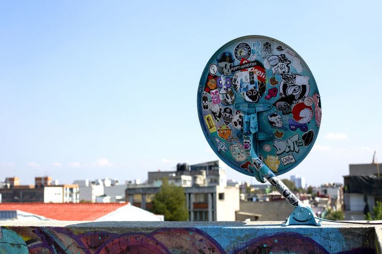 Close-up of ferris wheel against buildings in city