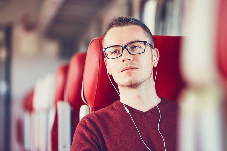 Young Man Listening To Music While Traveling In Train