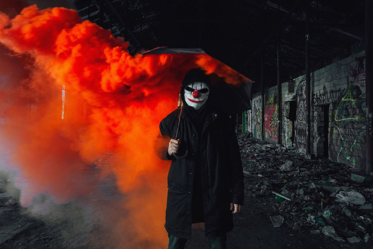 Person wearing a scary mask and red smoke