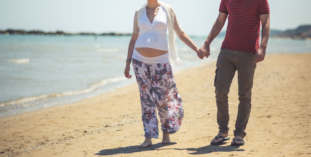 Low Section Of Man Holding Pregnant Woman Hands At Beach