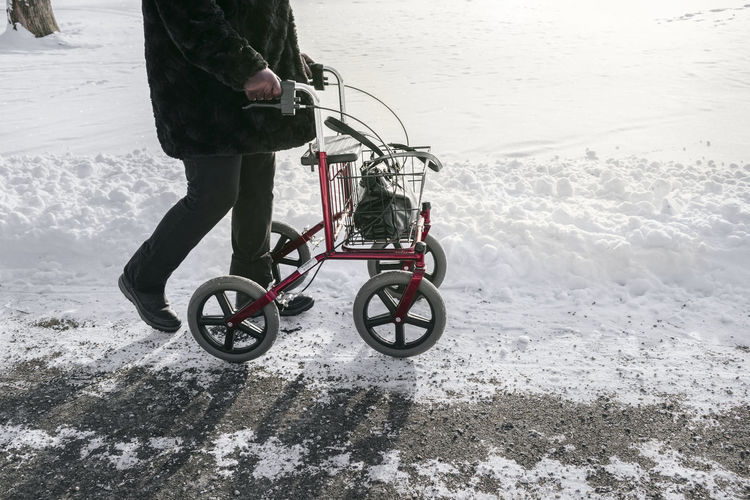 Low section of person riding bicycle on snow