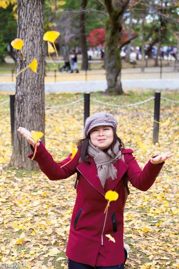 Portrait of woman throwing leaves in park