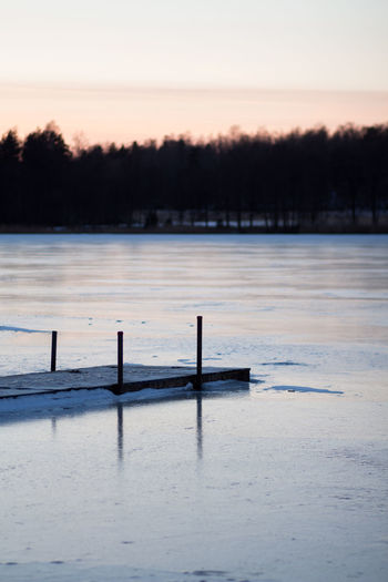 Water Tranquil Scene Sky Beauty In Nature Scenics - Nature Sunset Cold Temperature Lake Nature Winter Tree No People Wood - Material Non-urban Scene Waterfront Frozen Outdoors Bridge Over Water Bridge Ice On Lake Winter Lake Winter In Sweden Frosty Evening