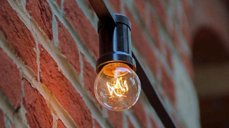 Low Angle View Of Illuminated Light Bulb On Brick Wall