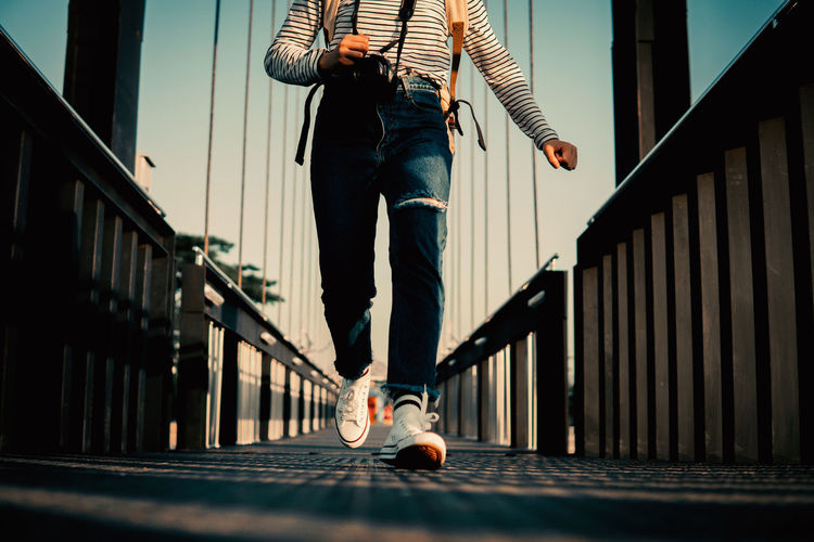 Low section of man standing on bridge
