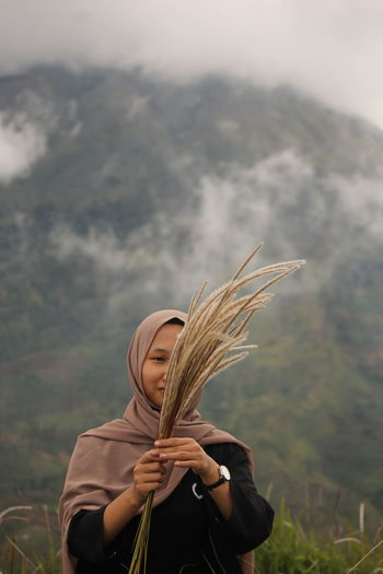 Woman holding plants while standing against mountain
