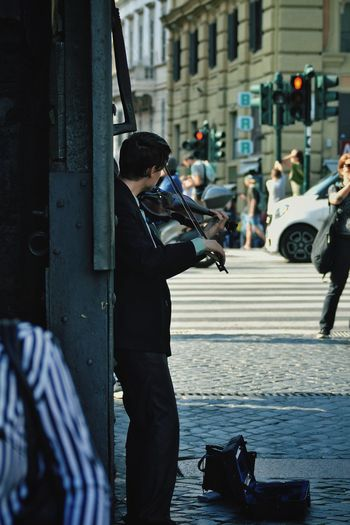 Street musician playing violin against wall