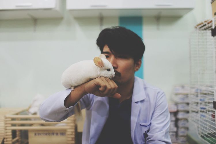 Veterinarian Holding Rat While Sitting In Hospital