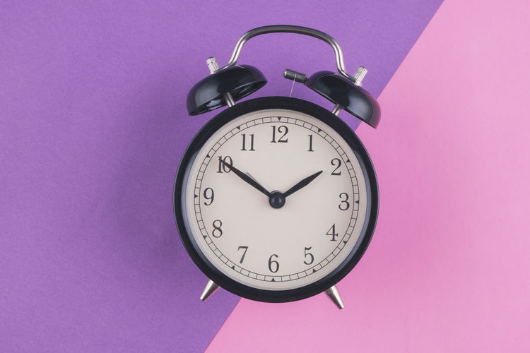 alarm clock on purple background Time Clock Indoors  Pink Color Instrument Of Time No People Accuracy Colored Background Alarm Clock Minute Hand Purple Number Still Life Close-up Studio Shot Wall - Building Feature Pink Background Low Angle View Clock Face Shape