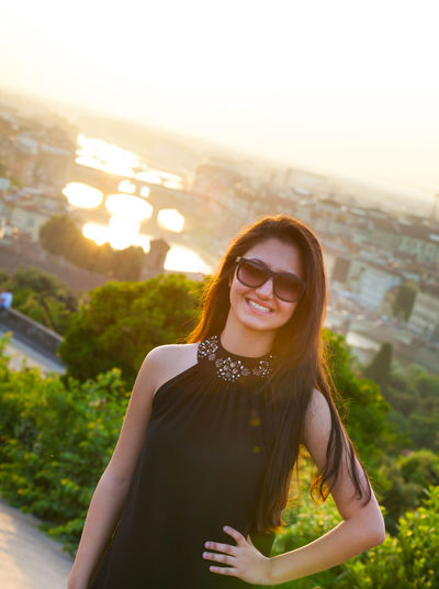 Portrait of smiling young woman standing against cityscape
