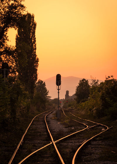 Railroad tracks against orange sky