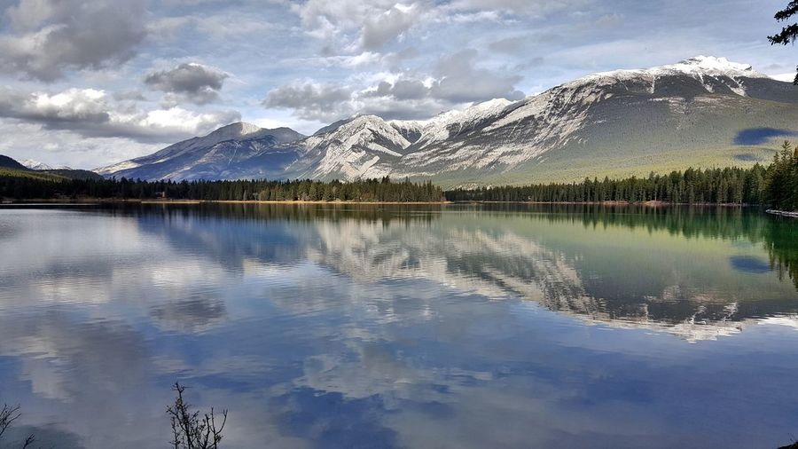 Scenic view of calm lake by mountains against cloudy sky